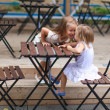 Little happy girls have fun at outdoor cafe — Stock Photo #47582517