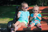 Two little adorable sisters eating ice cream outdoors — Stock Photo