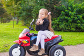 Little cute girl in leather jacket sitting on her toy motorcycle — Stock Photo
