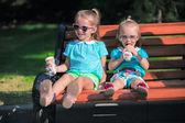 Две очаровательные девочки, едят мороженое на улице — Стоковое фото