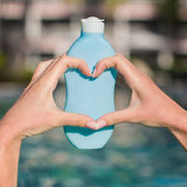 Close up of sunblock in female hands making heart — Stock Photo