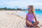 Adorable little girl sitting in a lotus position on an exotic beach — Stock Photo
