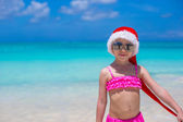 Little adorable girl in red Santa Hat on tropical beach — Stock Photo