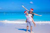 Gelukkige paar dragen kerstmuts hebben plezier op caribisch strand — Stockfoto