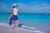Moeder en haar dochtertje wandelen op tropisch strand — Stockfoto