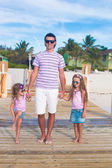 Family of three on wooden jetty by the ocean — Stock Photo