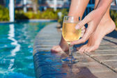 Female legs and glass of white wine near the pool — Stock Photo