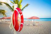 Red lifebuoy on the white sand beach — Stock Photo