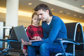 Father and little girl with laptop at the airport while waiting his flight — Stock Photo