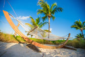 Straw hammock in the shadow of palm on tropical beach by sea — Stock Photo