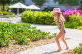 Adorable little girl at hat and swmsuit in exotic resort — Stock Photo