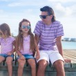 Family of three sitting on wooden dock enjoying ocean view — Stock Photo #47900581