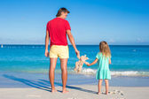 Young father with little girl holding a plush rabbit on exotic beach — Stock Photo