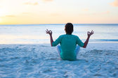 Young man sitting in the lotus position on white sand beach — Stock Photo