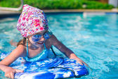 Little girl swimming on a surfboard in swimmingpoll — Stock Photo