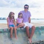Family of three sitting on wooden dock enjoying ocean view — Stock Photo #47992523