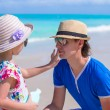 Little girl gets sun cream on her fathers nose — Stock Photo #47992525