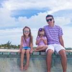 Family of three on wooden dock enjoying ocean view — Stock Photo #47992537
