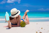 Smiling young woman applying sun cream on beach — Stock Photo