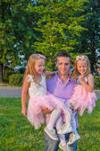 Young Father and his adorable daughters having fun outdoors — Stock Photo