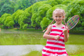 Cute little girl playing badminton on picnic — Stock Photo