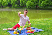 Young happy man picnicking and relaxing outdoors — Stock Photo