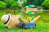 Picnic basket with fruits, bread and hat on straw bag — Stock Photo