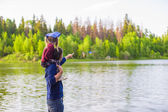 Young father and little adorable girl fishing on the river — Stock Photo