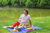 Young happy man picnicking and relaxing in the park — Stock Photo