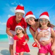 Portrait of happy family on the beach with christmas hats — Stock Photo
