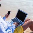 Young businessman using laptop and telephone on tropical beach — Stock Photo #49977351