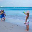 Little girl playing with family at the beach — Stock Photo #49977793