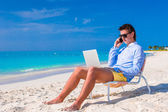 Young businessman using laptop on tropical beach — Stockfoto