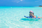 Little cute girl swimming on a surfboard in the turquoise sea — Stock Photo