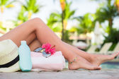 Suncream, hat, sunglasses, flower and tanned female legs near pool — Stok fotoğraf