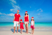 Family of four in Santa Hats having fun on tropical beach — Stock Photo