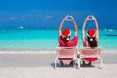 Happy romantic couple in red Santa Hats at beach making hearts — Stock Photo