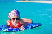 ターコイズ ブルーの海でサーフボードに愛らしい少女 — ストック写真