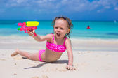 Happy little girl playing with toys at beach during vacation — Stock Photo