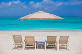 White umbrellas and sunbeds at tropical beach — Stock Photo
