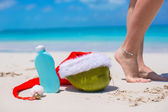Suncream, Santa Hat on coconut and tanned female legs at white beach — Stock Photo