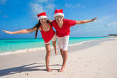 Beautiful couple in Santa hats on tropical beach have fun — Stok fotoğraf