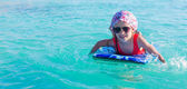 Little adorable girl on a surfboard in the turquoise sea — Stockfoto