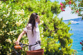 Young woman on summer vacation biking at tropical island — Стоковое фото