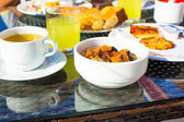 Delicious breakfast with flakes,dried fruit and cup of tea — Stock Photo