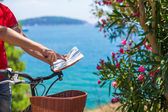 Young traveling man with map of the island bicycling — Stock Photo