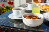 Tasty breakfast with flakes,dried fruit and cup of tea — Stock Photo