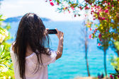 Back view of young woman taking photo with phone on beautiful bay — Stock Photo