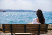 Young attractive woman on the bench during summer vacation — Stock Photo