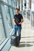 Man holding passport and boarding pass at airport waiting the flight — Stock Photo
